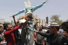 FILE - Indians burn an effigy of Pakistan and shout anti-Pakistan slogans during a protest in Ahmadabad, India, May 3, 2017.