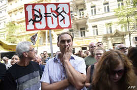 A protester holds a placard Aug. 21, 2018, in Prague, during commemorations marking the 50th anniversary of the Soviet invasion of former Czechoslovakia in 1968.