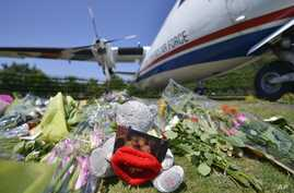 Flowers and a teddy bear are placed in front of a plane prior a ceremony to mark the return of the first bodies of passengers and crew killed in the downing of Malaysia Airlines Flight 17, Eindhoven military air base, July 23, 2014.