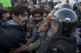 A civil society activist argues with police officers during a rally demanding recovery of the missing persons in Karachi, Pakistan, Thursday, Jan. 19, 2017. Pakistani police say a clash has been averted between the supporters of missing human rights