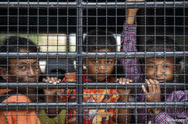 Cambodian migrants look through grills of a truck as they wait to cross the Thai-Cambodia border at Aranyaprathet in Sa Kaew June 15, 2014. The International Organization for Migration (IOM) estimates that over the past week 100,000 Cambodians have p