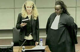 Actress Mia Farrow, left, is seen holding the bible being sworn on a screen in the pressroom of the U.N.-backed Special Court for Sierra Leone in Leidschendam, Netherlands, 09 Aug 2010