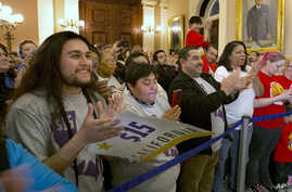 Supporters of a bill to raise California's minimum wage celebrate outside the state Senate Chamber after the measure was approved by the Senate, March 31, 2016, in Sacramento, California.