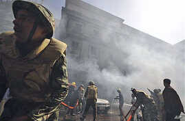 Egyptian army soldiers fight a fire believe to be set by hundreds of low-ranking police at a part of the security headquarters in Cairo, Egypt, February 23, 2011