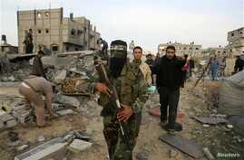 A Palestinian Hamas militant walks in the rubble of the destroyed house of Hamas militant Mohammad Abu Shmala, following an Israeli air strike in Rafah, southern Gaza Strip, November 16, 2012.