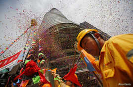 A worker attends the topping out ceremony as crane lift the last piece of steel at the Shanghai Tower, which is undergoing construction at the financial district of Pudong in Shanghai Aug. 3, 2013.