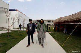 Rahmatullah Amiri, right, a political science student of American University of Afghanistan who was injured in last year's attack, arrives for new orientation sessions at a American University in Kabul, Afghanistan, March 27, 2017.