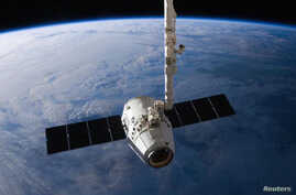 FILE - The SpaceX Dragon cargo capsule approaches the International Space Station prior to installation in this NASA picture taken April 10, 2016.