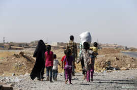 A displaced family from the minority Yazidi sect walks towards the entrance of Mosul, Aug. 21, 2014.