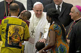 "Pope Francis greets a family in the Paul VI hall at the Vatican at the end a meeting with participants in the ""Evangelii Gaudium"" conference organized by the Pontifical council for the new evangelization, Sept. 19, 2014."