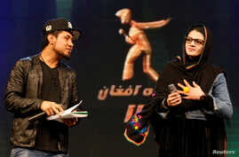 Zulala Hashimi, 18 (R) and Sayed Jamal Mubarez, 23 (L) singer finalists of the music contest 'Afghan Star', rehearse for the show in Kabul, Afghanistan, March 19, 2017.