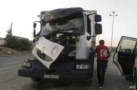This image provided by the Syrian Arab Red Crescent shows the aftermath of an attack on a humanitarian aid convoy that came under fire shortly before dark Saturday, June 17, 2017, outside Damascus, Syria.