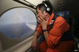 Koji Kubota of the Japan Coast Guard keeps watch while flying in the search zone for debris from flight MH370, April 1, 2014.