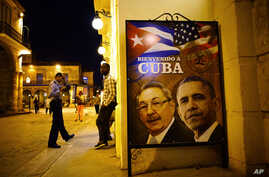 """A poster features portraits of Cuba's President Raul Castro, left, and U.S. President Barack Obama and reads in Spanish """"Welcome to Cuba"""" outside a restaurant in Havana, Cuba, March 17, 2016."""