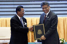 Cambodia's PM Hun Sen, left, with ASEAN Secretary-General Surin Pitsuwan after the ceremony for the adoption of the ASEAN Human Rights Declaration,  during the ASEAN Summit in Phnom Penh, November 18, 2012.
