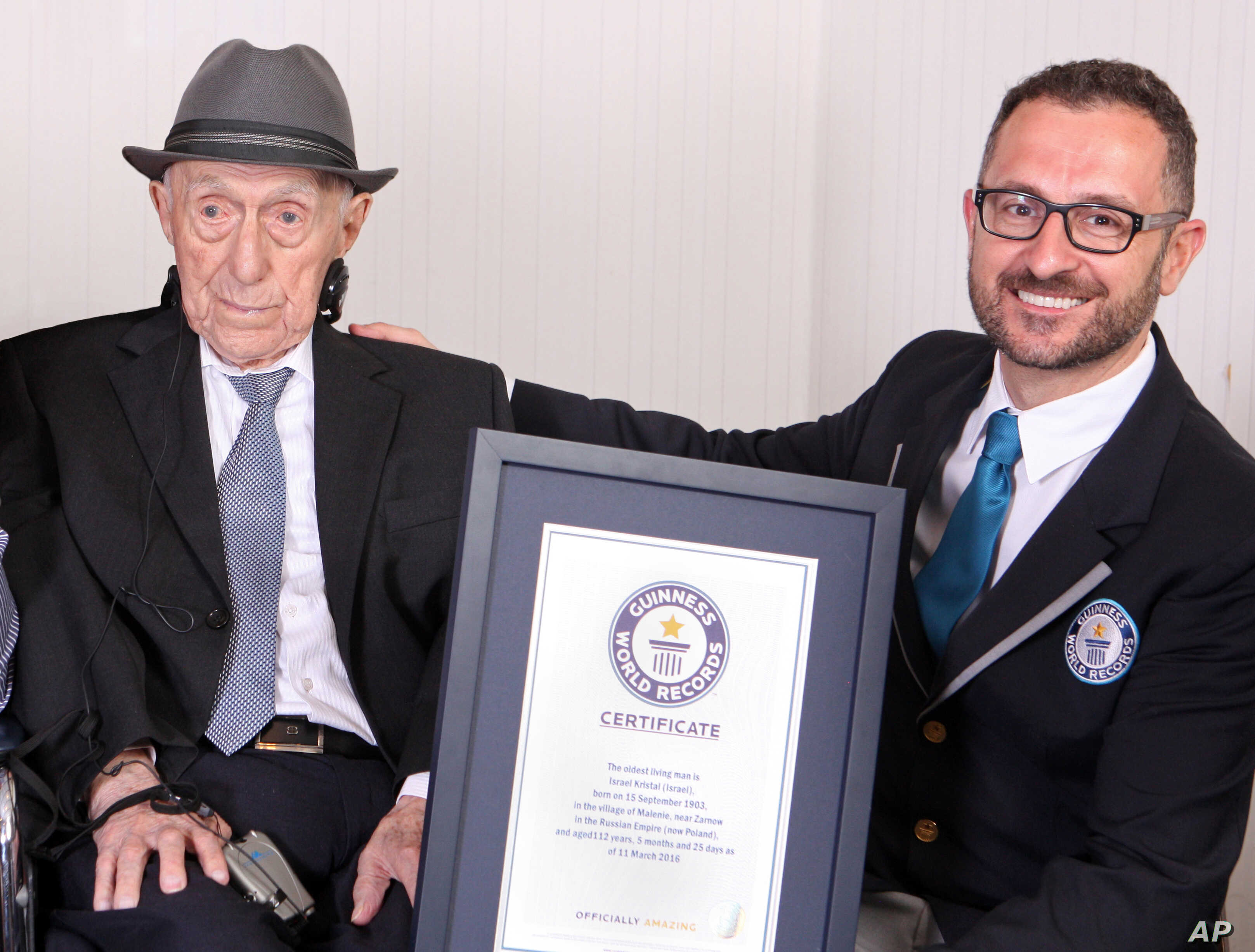 In this photo supplied by Guinness World Records, Marco Frigatti, head of records for Guinness World Records, presents Israel Kristal a certificate for being the oldest living man, in Haifa, Israel, March 11, 2016.