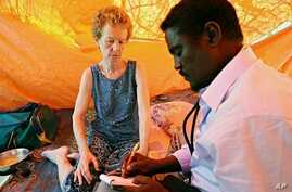 A photo made on 28 Jan 2010 shows Briton Rachel Chandler (L) being examined by Somali doctor Abdi Mohamed Helmi (R) at a location in central Somalia, where she is being held since she and her husband Paul were kidnapped as they sailed their yacht, th