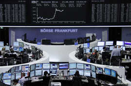 Traders are pictured at their desks in front of the DAX board at the Frankfurt stock exchange, Aug. 14, 2014.