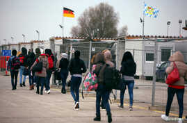 Eritrean migrants walk after arriving by plane from Italy at the first registration camp in Erding near Munich, Germany, Nov. 15, 2016.
