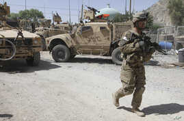 A US soldier, part of the NATO forces, patrols a police station after it was attacked by militants in Kandahar, south of Kabul, Afghanistan,  June 19, 2012.