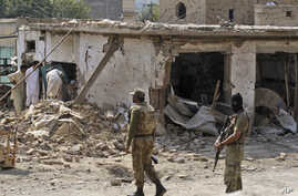 Pakistani men check the damage caused by a car bomb explosion, while army soldiers gather at the site in the town of Darra Adam Khel in the troubled Khyber Pakhtunkhwa province bordering Afghanistan, October 13, 2012.