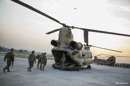 FILE - U.S. soldiers from the 3rd Cavalry Regiment load into a CH-47 Chinook helicopter for an advising mission to an Afghan National Army base at forward operating base Fenty in the Nangarhar province of Afghanistan, Dec. 21, 2014.