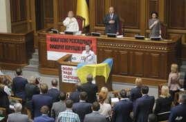 Ukrainian military pilot Nadiya Savchenko, center, and lawmakers sing the national anthem during a parliament session in Kyiv, Ukraine, May 31, 2016. Savchenko appeared for her first session at the Ukrainian parliament after being released last week