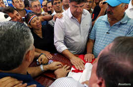 Efrain Alegre, president of the Liberal Party, and other activists react next to the casket with the remains of Rodrigo Quintana, who was killed early Saturday by a rubber bullet fired by the police in the headquarters of the Liberal Party, after cl