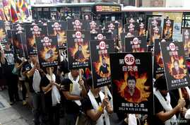 Activists display portraits of people who killed themselves by self-immolation take part in a rally to support Tibet, Taipei, Taiwan, March 10, 2013.