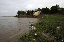 FILE - A Cambodian fisherman takes off his fishing net at Mekong river bank of Koh Norea village in Phnom Penh, Cambodia.
