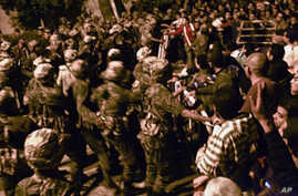 Hundreds of protesters, trying to break in the state security headquarters, are contained by Egyptian soldiers in Cairo on March 6, 2011.
