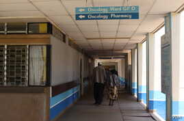 FILE - A patient accompanied by a visitor is seen walking inside Kenyatta National Hospital in Nairobi, Kenya. According to the country's Ministry of Health, every year more than 28,000 people die of cancer and about 41,000 new cases are diagnosed ...