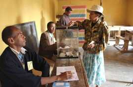 A resident of the Madagascar's capital, Antananarivo, casts her vote at a local polling station, 17 Nov 2010
