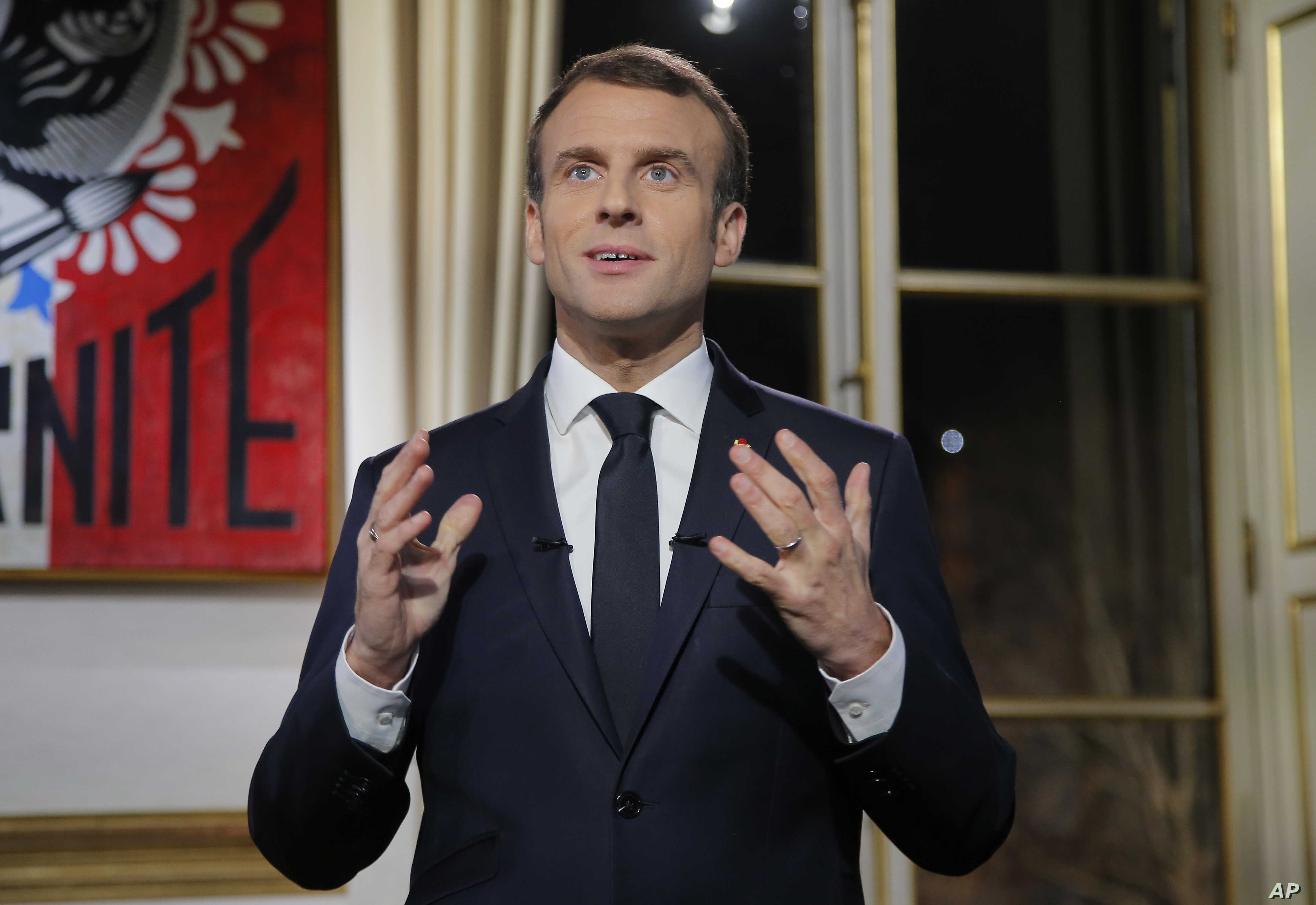 French President Emmanuel Macron, gestures as he poses for a photograph after the recording of his New Year's speech at the Elysee Palace, in Paris, Dec. 31, 2018.