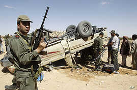A Tunisian army soldier stands guard near an overturned car which belongs to forces loyal to Libyan leader Moammar Gadhafi after clashes with Tunisians and rebel fighters in Dehiba near the Libyan and Tunisian border crossing of Dehiba, April 29, 201
