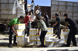 Syrian men carry aid parcels provided by the UN World Food Programm (WFP) and the Syrian Arab Red Crescent in the rebel-held town of Al-Houla, on the northern outskirts of Homs in central Syria, on May 25, 2016.
