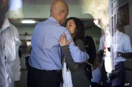 Former Haitian President Michel Martelly, left, comforts Patricia Preval, the daughter of Haiti's late former President Rene Preval, at the Sainte Claire hospital in Petion-Ville, Haiti, March 3, 2017.