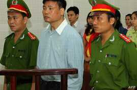 Blogger Truong Duy Nhat (C) stands trial at a local People's Court in the central city of Da Nang, March 4, 2014.