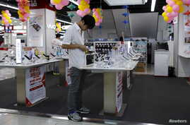 FILE - A customer look at a mobile phone on display at an electronics market in Shanghai, China.