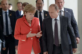 Russian President Vladimir Putin (R) and German Chancellor Angela Merkel speak to each other before the World Cup final between Germany and Argentina in Rio de Janeiro, Brazil.
