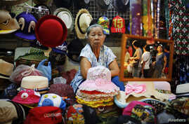 FILE - Souvenirs are offered to tourists visiting the Amphawa floating market at Samut Songkhram province, Thailand. In Thailand, over 10 percent of the 67 million population is 65 years or older.