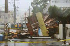 A wooden house that collapsed due to strong winds caused by Typhoon Neoguri is seen in Naha, on Japan's southern island of Okinawa, in this photo taken by Kyodo, July 8, 2014.
