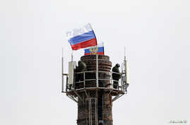 Armed men, believed to be Russian servicemen, stand guard at the top of a chimney located near the naval headquarters, with Russian flags installed nearby, in Sevastopol, March 19, 2014.
