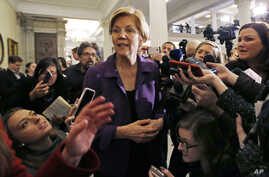 Democratic Sen. Elizabeth Warren is surrounded by reporters at the Massachusetts Statehouse, Jan. 2, 2019, in Boston.