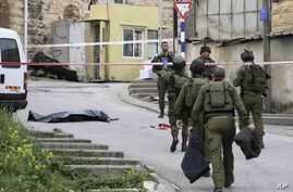 FILE - In this Thursday, March 24, 2016 file photo, Israeli soldiers stand near the body of a Palestinian who was shot and killed by a soldier while laying wounded on the ground after a stabbing attack in Hebron, West Bank.
