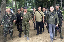 President Rodrigo Duterte, center left, wearing a cap and an assault rifle slung on his shoulder, walks with other military officers and security men inside the camp of the 2nd Mechanized Infantry Brigade, Light Armored Division, July 7, 2017 in the