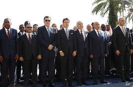Italian Premier Giuseppe Conte, center, is flanked by Fayez Serraj, the PM of the U.N.-backed government in Tripoli, left, and UN special envoy for Libya, Ghassam Salame', as they pose for a family photo in Palermo, Nov. 13, 2018.
