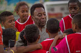 FILE - Legendary Brazilian former football player Pele speaks with children during the inauguration ceremony of the new technology football pitch installed at Mineira favela in Rio de Janeiro, Brazil, Sept. 10, 2014.