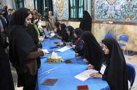 Iranian voters, left, arrive at a polling station to vote for their country's parliamentary and Experts Assembly elections as election staff receive them in Tehran, Iran, Feb. 26, 2016.
