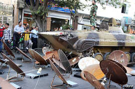 Iranian soldiers destroying satellite dishes with an army tank in the southwestern city of Shiraz. Iranian authorities carry out regular crackdowns to remove satellites from rooftops, and issue warnings against their use, September 28, 2013.